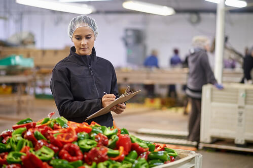 Logistics employee filling out a time-consuming produce inspection checklist