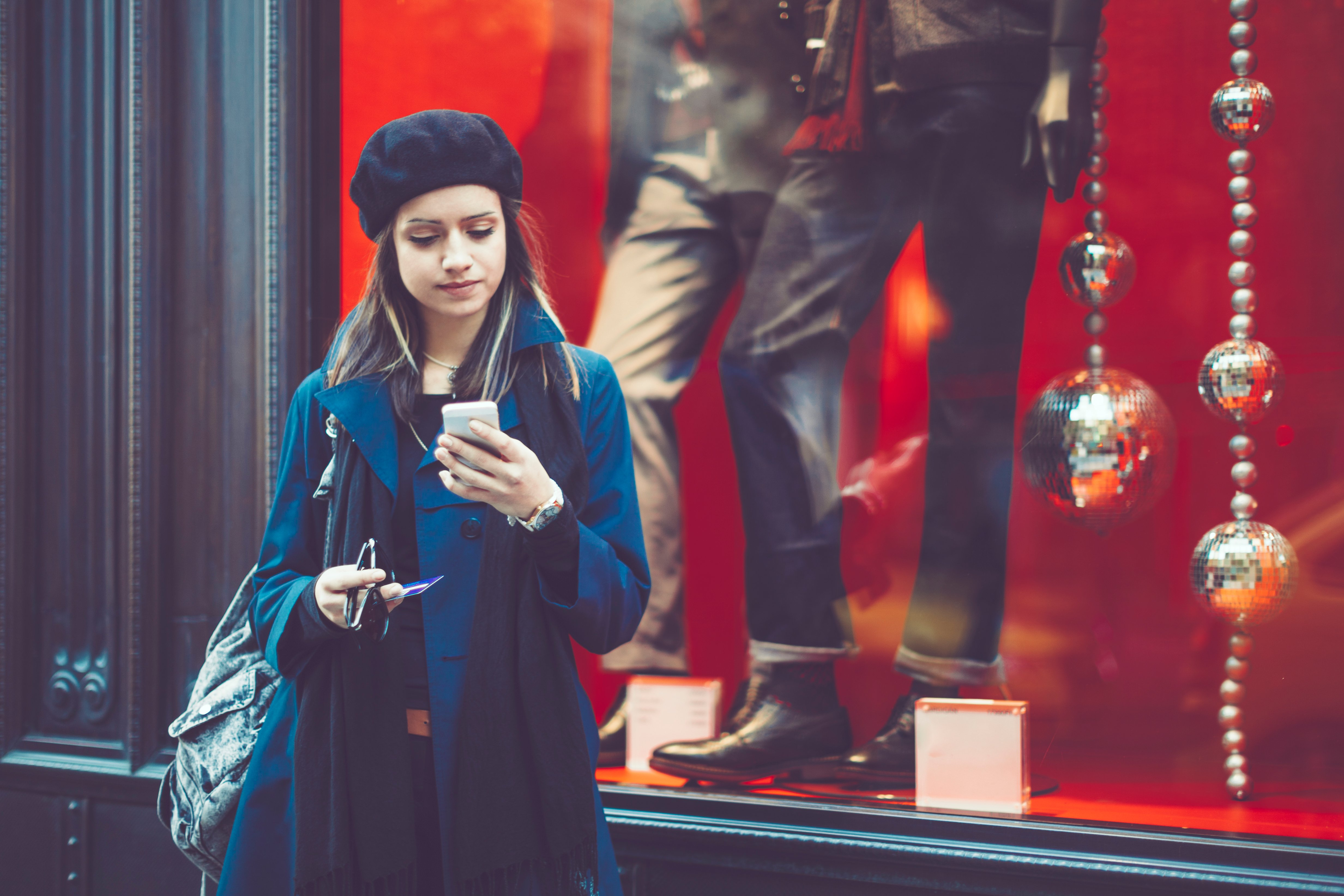 Woman-with-mobile-phone-in-front-of-shop-window